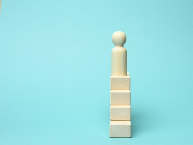 한 남자의 나무 입상이 맨 위에 블록 사다리 위에 서 있습니다. 비즈니스, 경력 성장에서 설정된 목표를 달성하는 개념.