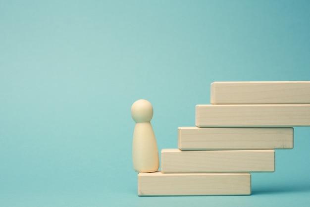 한 남자의 나무 입상이 첫 번째 단계에서 블록으로 만들어진 계단에 서 있습니다. 비즈니스, 경력 성장, 스타트 업에서 설정된 목표를 달성하는 개념