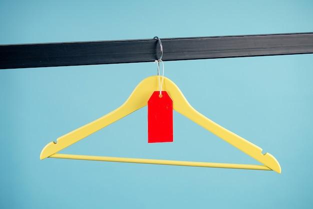 나무 옷걸이와 빨간색 라벨(탭, 태그, 탈리)이 스튜디오의 파란색 배경에 있는 철제 옷장에 걸려 있습니다. 계절 판매 및 할인의 개념