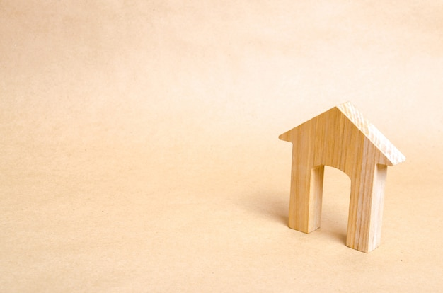 Деревянный дом с большим дверным проемом стоит на бежевом фоне бумаги.