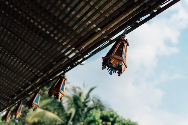 木製のランタンが木製のバルコニーからぶら下がっていて、空を背景にしています。