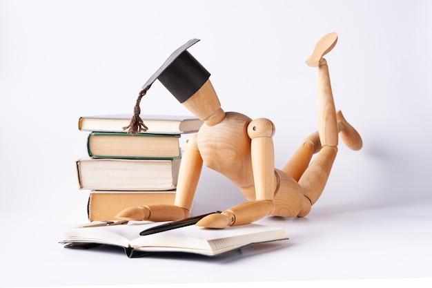Деревянный человек в студенческой шляпе лежит на полу и читает учебники