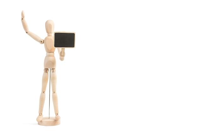 Деревянный манекен-игрушка держит небольшую доску на белом фоне с копией пространства
