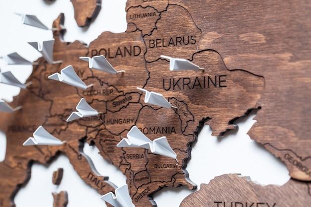 世界の木製の地図が壁に接着されており、訪問した国のマークが付いています