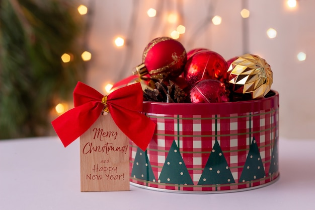 赤い弓とテキストの木製のメモメリークリスマスと新年あけましておめでとうございます丸いブリキの箱のおもちゃのボール