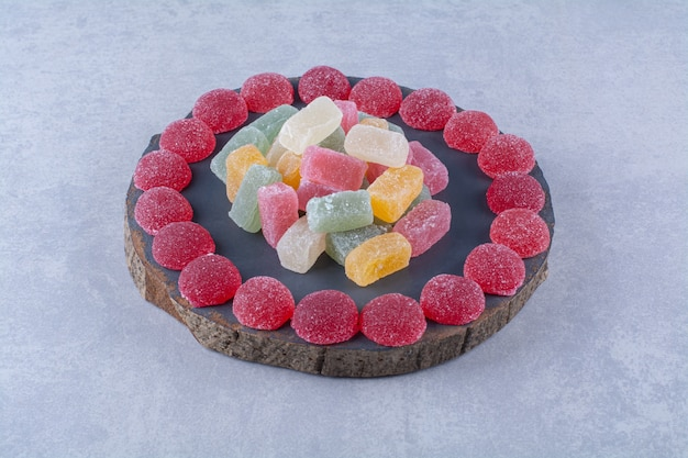 다채로운 설탕 젤리 캔디가 가득한 나무 조각 보드