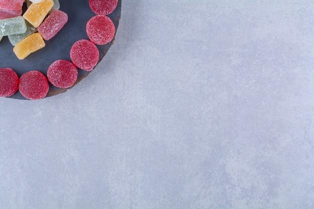 カラフルな甘いゼリーキャンディーがいっぱいの木片ボード