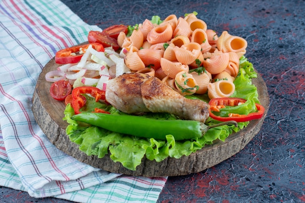 야채 샐러드와 함께 맛있는 닭 다리 고기의 나무 조각.
