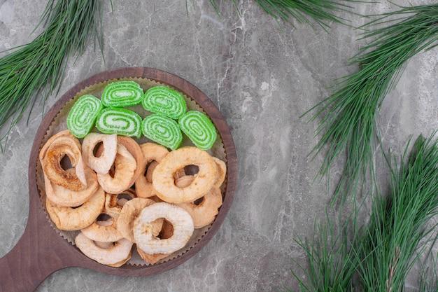 달콤한 녹색 마멀레이드와 말린 사과 과일의 나무 조각. 프리미엄 사진