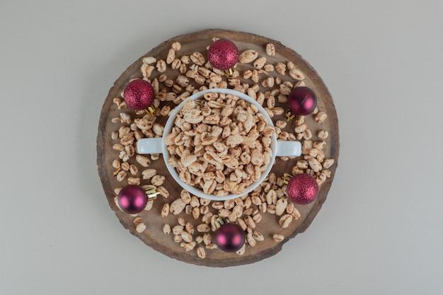 Деревянная тарелка, полная здоровых хлопьев с елочными шарами.