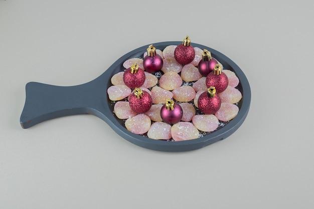 クリスマスボールが付いたハート型のゼリーキャンディーがいっぱいの木のプレート。