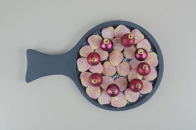 Деревянная тарелка, полная желейных конфет в форме сердца с елочными шарами.