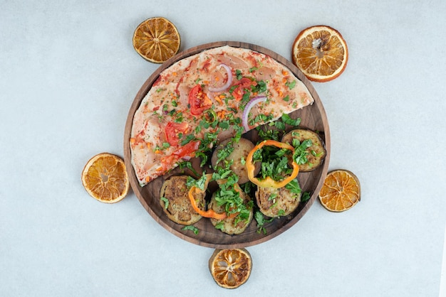 Деревянная тарелка, полная лаваша с нарезанными баклажанами.