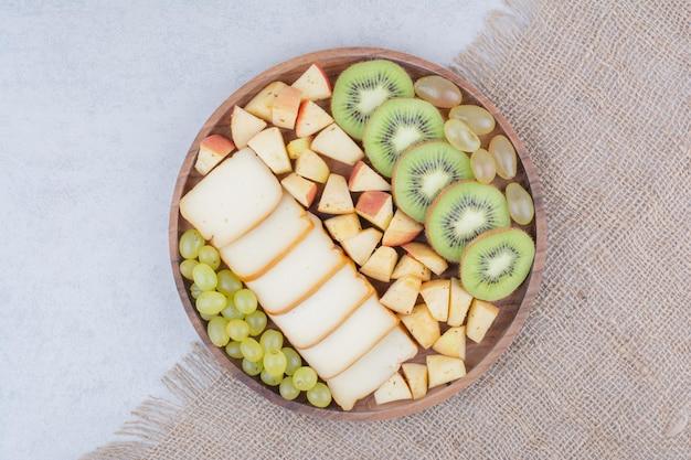얇게 썬 과일과 빵이 가득한 나무 접시. 고품질 사진