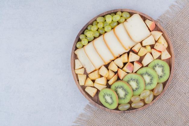 Деревянная тарелка, полная нарезанных фруктов и хлеба. фото высокого качества