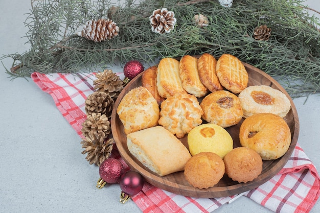 크리스마스 공과 솔방울이 있는 달콤한 페이스트리로 가득한 나무 접시