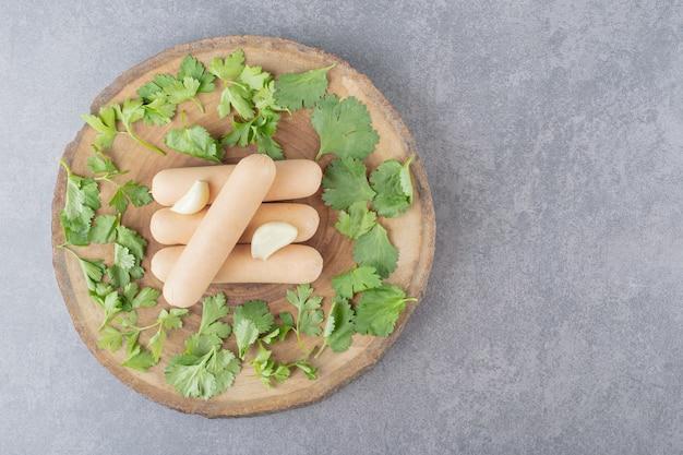파슬리와 마늘을 곁들인 삶은 소시지 나무 접시