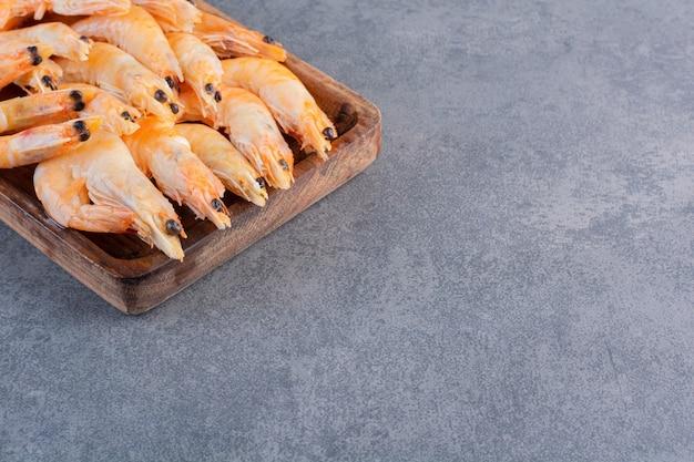 Деревянная тарелка вкусных креветок на каменной поверхности