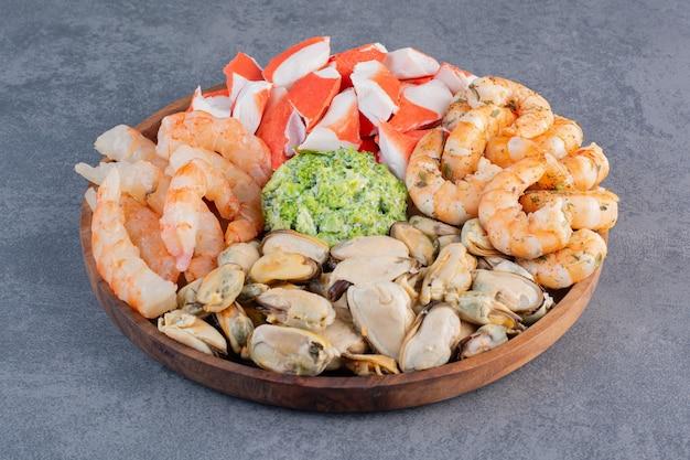 Деревянная тарелка вкусных креветок с вкусными крабовыми палочками на каменном фоне.