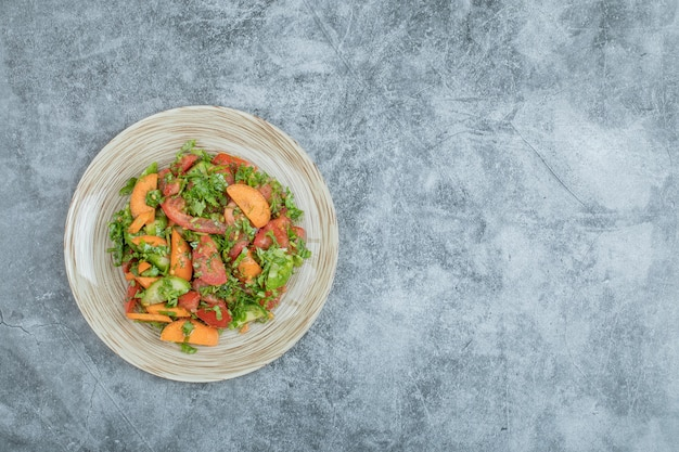Деревянная тарелка вкусного овощного салата.