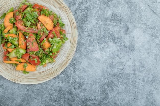 맛 있는 야채 샐러드의 나무 접시입니다.