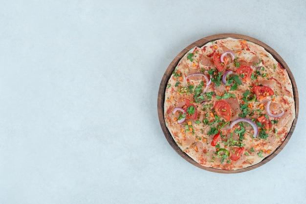 얇게 썬 토마토와 양파를 곁들인 피타 빵 나무 접시.