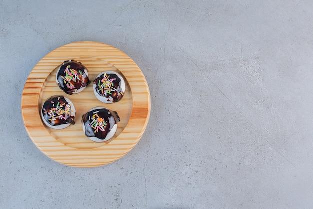 Деревянная тарелка вкусного глазированного печенья на каменном столе.