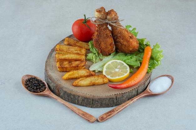 大理石のテーブルの上に揚げたcgickenと野菜の木製プレート。