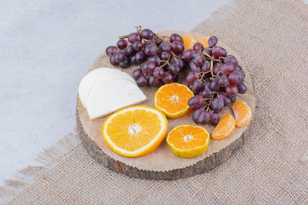 Деревянная тарелка с нарезанным сыром и фруктами. фото высокого качества