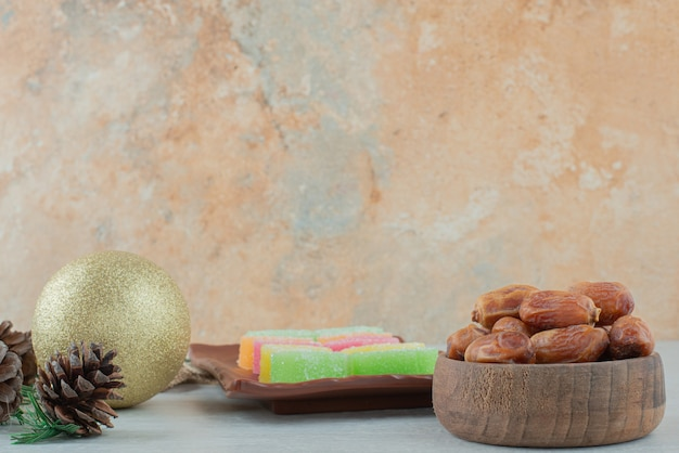 Деревянная миска, полная сухофруктов и мармелада на мраморном фоне. фото высокого качества
