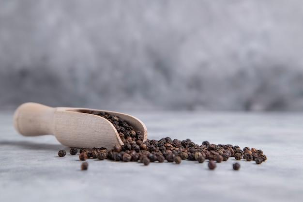 Деревянная ложка, полная зерен черного перца, поставлена на каменный стол. фото высокого качества