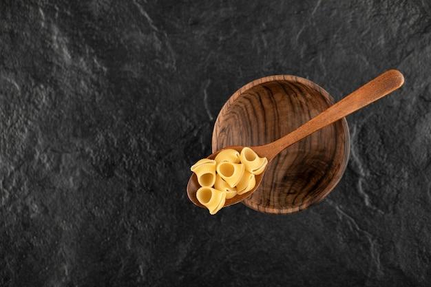 未調理のコンキリエマカロニの木のスプーン。