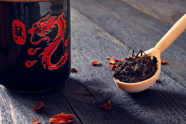 ヴィンテージの暗い板のテーブルに赤いドラゴンの写真が描かれた黒いマグカップの横に、黒いリーフティーが入った木のスプーンがあります。