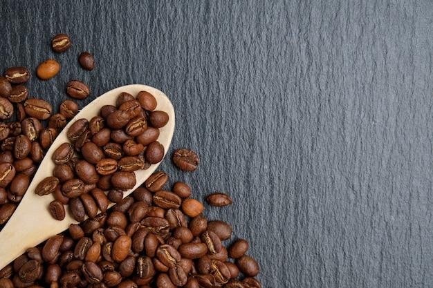 Деревянная ложка с кофейными зернами на фоне грифельной доски
