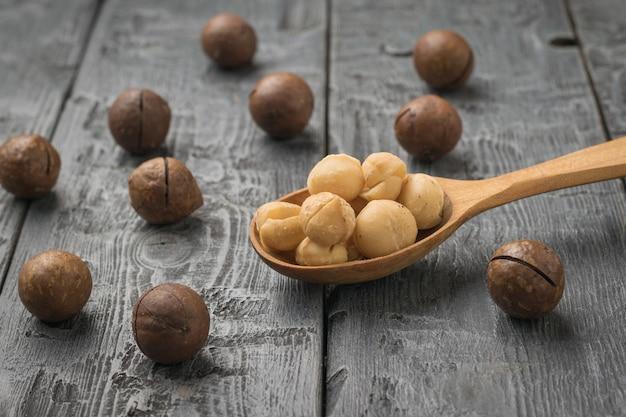 皮をむいたマカダミアナッツと散らばった皮をむいていないナッツが入った木のスプーン。スーパーフード。