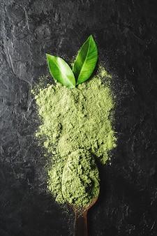 Деревянная ложка с рассыпанным зеленым натуральным листовым порошком.