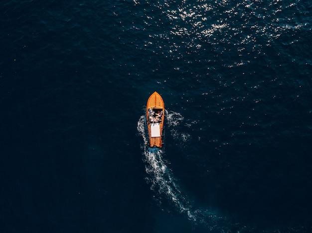 人々が乗船している木製のスポーツボートが海に乗ります。豪華な木製モーターボート-からの上面図