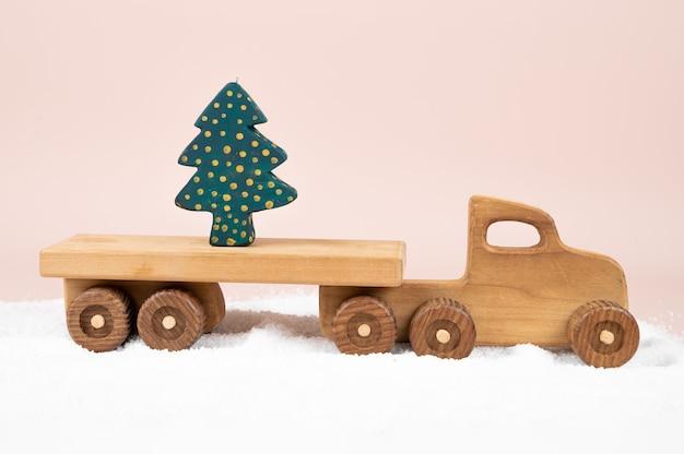 クリスマスツリーと木のおもちゃのトラック。コピースペース付きのクリスマスカード。高品質の写真