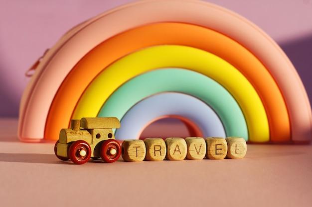 Деревянный шлейф с кубиками с надписью путешествия на фоне объемной яркой радуги.