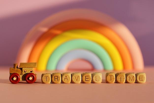 Деревянный шлейф с кубиками с надписью «время в пути» на фоне объемной яркой радуги.