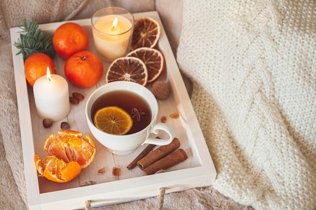 ベージュの格子縞にお茶、みかん、ナッツ、スパイスが入った木製トレイ。冬の朝食。ヒュッゲの概念。高品質の写真