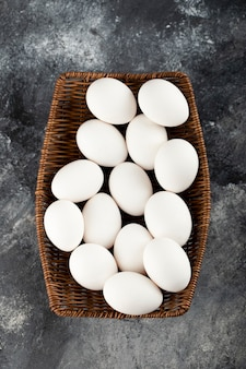 Деревянное плетение, полное белых сырых куриных яиц.