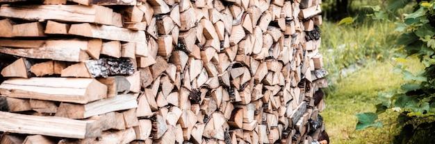 Поленница с заготовкой и сложенными дровами из рубленых дров для растопки и обогрева дома. дрова березы. знамя