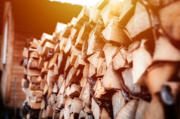 Поленница с заготовкой и сложенными дровами из рубленых дров для растопки и обогрева дома. дрова березы. вспышка