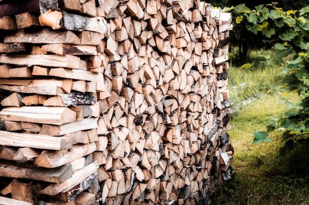 Поленница с заготовкой и сложенными дровами из рубленых дров для растопки и обогрева дома. дрова березы
