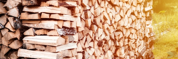 Поленница с заготовкой и сложенными дровами из колотых дров для растопки и обогрева дома.