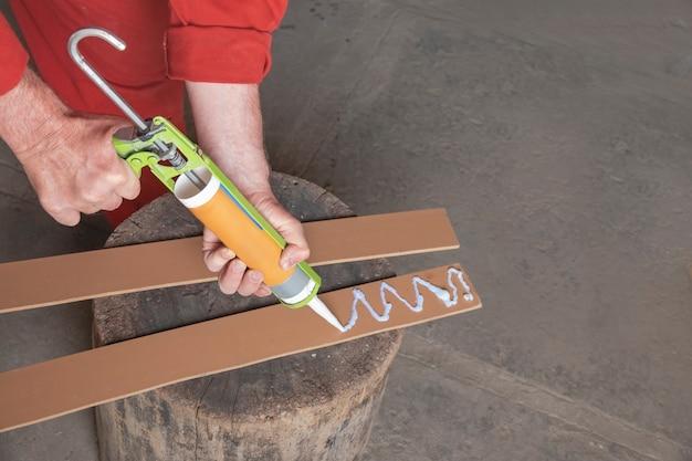 Рабочий наносит белый клей на полоски ламината ламинат плотник склеивает доски