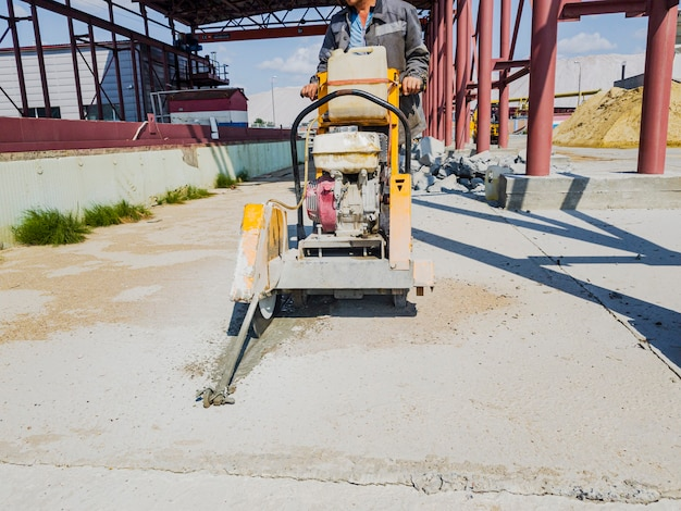 Рабочий на стройке режет бетон алмазной пилой. бетонолом