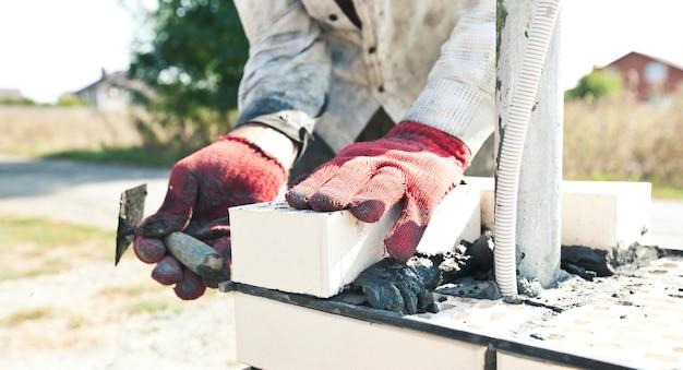Рабочий строит столб для забора из кирпича