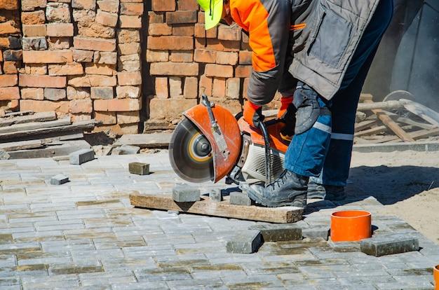 작업자가 가스 절단기와 손톱으로 포장 슬래브를 절단합니다.